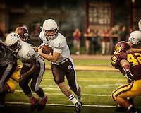 Mt Carmel quarterback Marko Borocich breaks through an opening for again in the first quarter against Loyola Saturday
