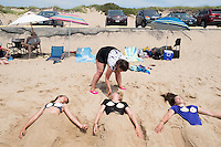 Sisters Chloe, 15, (center) and Amelie Lachance-Soulard, 16 (right), of Ottawa, Canada, and cousin Simone Soulard, 14, lay buried under sand sculptures of mermaid tails at Herring Cove Beach in the Cape Cod National Seashore outside of Provincetown, Mass., USA, on Fri., July 1, 2016. The sisters' mother Pascale Lachance, of Ottawa, adjusts Chloe's hair. Portions of the parking lot have been closed after land eroded during storms earlier this year. This was the girls' first visit to the area.