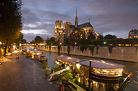 Notre Dame cathedral & Quai de la Tournelle, from Pont de L'Archeveche, Paris, France evening with bateaux restaurantss