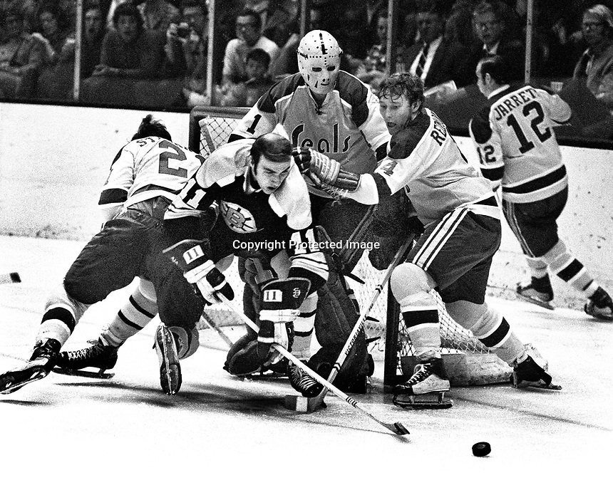 Seals Ron Stackhouse and Dick Redmond help goalie.Gary Smith against the Boston Bruins, Wayne Carleton #11.(1971 photo/Ron Riesterer)