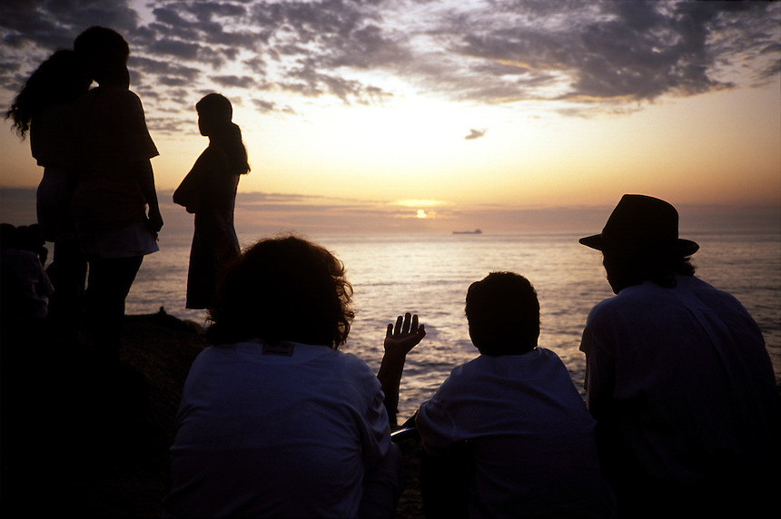 A small crowd gathered on a rocky point at Ipanema beach watches the sun rise on the first day of the year. Rio's traditional New Year revelers head to the beach to watch the sun rise after the long night of celebration.