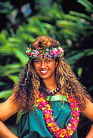 Lovely upper torso photo of a smiling beautiful Polynesian woman wearing kukui nut, haku and flower lei against a backdrop of tropical green foliage.
