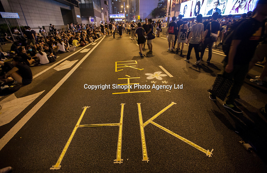 'Democracy Hong Kong' is seen marked on the road on the second day of the mass civil disobedience campaign Occupy Central, Central District, Hong Kong, China, 30 September 2014. The movement is also being dubbed the 'umbrella revolution' after the versatile umbrellas used to shield protesters from rain, sun - and police pepper spray.