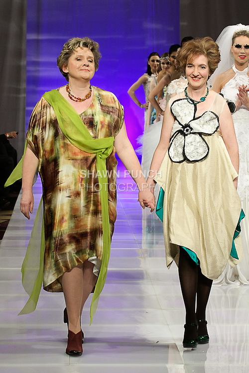 Fashion designer Ruby Johnson (left) and jewelry designer Jolanta Warpechowska-Gruca walk runway at the close of the Rudy Ellen Designs Fall 2013 haute couture collection fashion show, during Couture Fashion Week in New York, February 15, 2013.