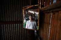 "U Mon Gyit, a 35 year old Muslim Burmese refugee is reflected in the mirror at his food shop at the Mae La refugee camp near Mae Sot June 3, 2012. Asked about Aung San Suu Kyi's visit to the camp U Mon Gyit said ""I saw her yesterday. We are only small people, we don't know can she make changes or not. But, even if she becomes the president I will still watch situation for years before deciding to go back."" Myanmar's pro-democracy leader Aung San Suu Kyi visited on Saturday Mae La, the biggest refugee camp along the Thailand-Myanmar border where tens of thousands of her compatriots found shelter after escaping from Myanmar.  REUTERS/Damir Sagolj (THAILAND)"