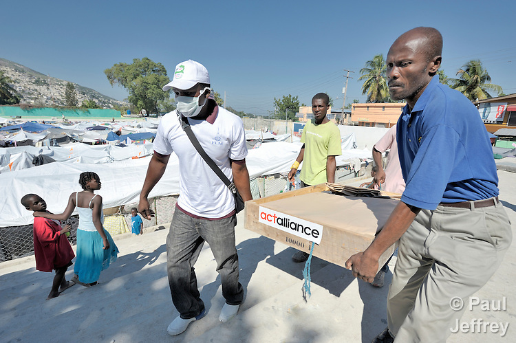 Emergency workers for the Lutheran World Federation, a member of the ACT Alliance, carry a water bladder into a crowded soccer stadium in the Santa Teresa area of Petionville, Haiti, where hundreds of families have constructed shelters. Hundreds of thousands of Haitians were left homeless by the January 12 quake.
