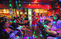 Prostitutes in the Rio Bar, the Angeles City 'girly bar' that British banker Rurik Jutting used to frequent, sit in their workplace after sharing their experience of the alleged murderer, Angeles City, Republic of the Philippines, 08 November 2014. The 'sin city', which sprung up on the fringes of a US Air Force base during the Vietnam war, has a reputation for cheap sex, and was a favourite destination for alleged murderer Rurik Jutting, who used to fly to Angeles City from Hong Kong for debauched weekends. The British banker is currently on remand at a secure facility in Hong Kong for allegedly murdering two Indonesian prostitutes in his flat whilst high on alcohol and cocaine.