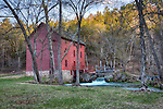 An old red mill sits at Alley Spring in Eminence, Missouri amid a variety of trees.