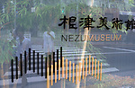 Passerby are reflected in the glass sign marking the entrance to the Nezu Museum of Art in, Tokyo, Japan on 17 Sept. 2012. Photographer: Robert Gilhooly