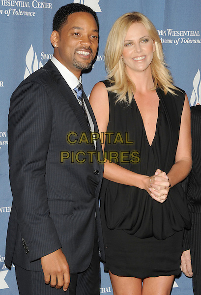 WILL SMITH & CHARLIZE THERON.The Simon Wiesenthal Center's 2009 National Tribute Dinner honoring Will Smith held at The Beverly Wilshire Hotel in Beverly Hills, California, USA. .May 5th, 2009                                                                     half length black suit jacket goatee facial hair dress sleeveless low cut neckline .CAP/DVS.©Debbie VanStory/Capital Pictures.