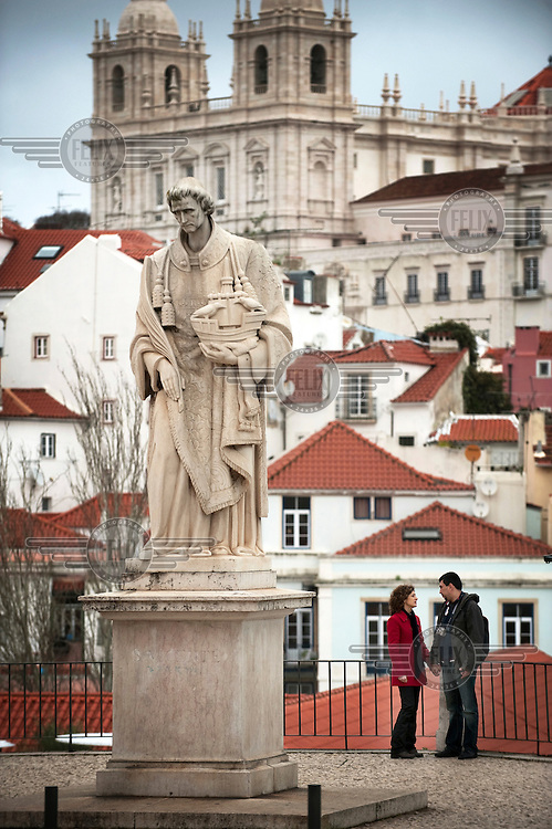 A tourist couple stand next to a religious statue in Lisbon's historic Alfama District.