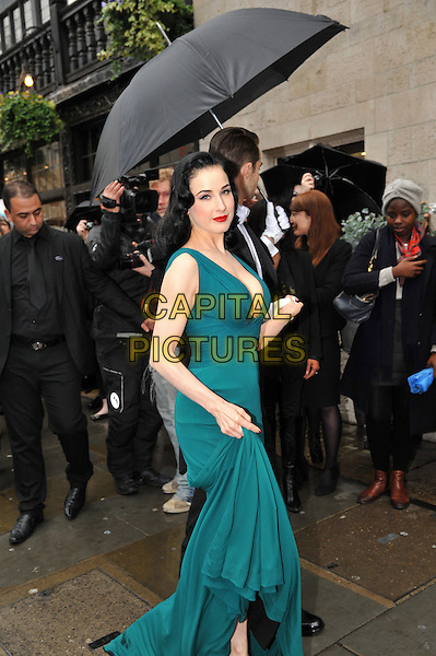 Dita Von Teese .Dita Von Teese, the burlesque superstar, appeared at Liberty London to launch her debut fragrance, named after herself, London, England..May 1st, 2012.perfume full length dress low cut neckline cleavage red lipstick teal blue green holding hands umbrella black suit white shirt gloves side.CAP/BF.©Bob Fidgeon/Capital Pictures.