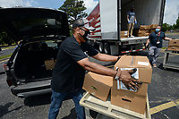 Hershell West, research program director for University of Arkansas for Medical Sciences Northwest, loads boxes of food Friday, June 19, 2020, in the back of a volunteer's car for non-contact delivery to families in quarantine and isolation in Benton and Washington counties at the UAMS Northwest facility in Fayetteville. The effort was coordinated by UAMS as a part of the Northwest Arkansas Equitable Food Response and Relief Project, which is funded by the Walmart Foundation and involved more than 50 volunteers. Food for the effort was donated by the Samaritan Community Center, Feed the 479, Second Street Pantry and the Northwest Arkansas Food Bank.Visit nwaonline.com/200620Daily/ for today's photo gallery.<br /> (NWA Democrat-Gazette/Andy Shupe)