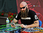 Chris Kael of Five Finger Death Punch signs autographs during the Trespass America Festival at Jacobs Pavilion at Nautica in Cleveland, Ohio.