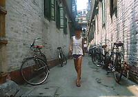 Cina, Pechino, ragazzo cammina in mezzo a biciclette negli hutong<br />