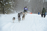 Kevin Raymond Cook passes by University Lake during the first day of the World Championship Sled Dog Races, a highlight of the 2013 Anchorage, Alaska, Fur Rendezvous.