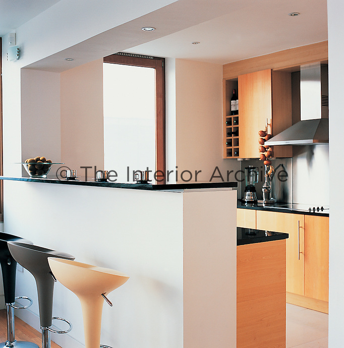 A breakfast bar separates the dining area from a kitchen, with its maple units and granite worktops.