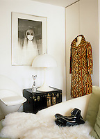 A white Verner Panton lamp sits on a black trunk beside a vintage coat on a mannequin in the living room