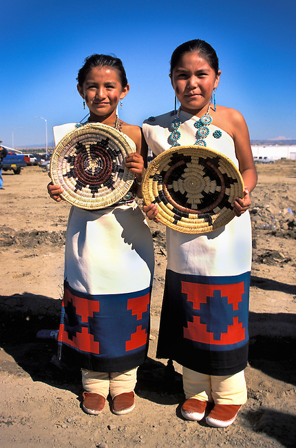 Two young participants of the Naatsiilio (Rainbow) Dancers are dressed in traditional Navajo cotton dresses adorned with turquoise and wearing Navajo moccasins and leggings hold traditional baskets. Shiprock, New Mexico.