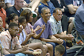 United States President Barack Obama, first lady Michelle Obama and daughters Malia Obama and Sasha Obama attend the Hawaiian Airlines Diamond Head Classic men's basketball game between the Oregon State Beavers and the University of Akron Zips at the University of Hawaii at Manoa Stan Sheriff Center, Sunday, December 22, 2013. The first lady's brother, Craig Robinson, is the Oregon State University Men's Head Basketball Coach.  At far right is Bobby Titcomb, one of the President's oldest friends.<br /> Credit: Cory Lum / Pool via CNP