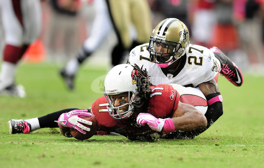 Oct. 10, 2010; Glendale, AZ, USA; Arizona Cardinals wide receiver (11) Larry Fitzgerald is tackled by New Orleans Saints safety (27) Malcolm Jenkins at University of Phoenix Stadium. The Cardinals defeated the Saints 30-20. Mandatory Credit: Mark J. Rebilas-