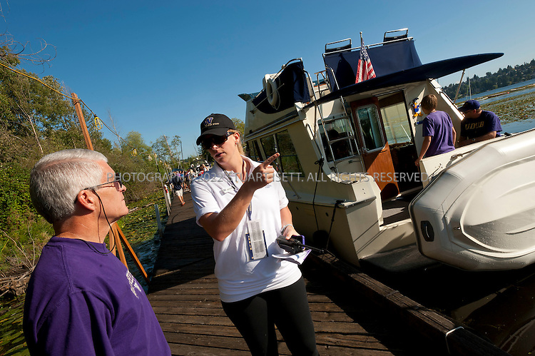 9/24/2011--Seattle, WA, USA...Staff from the UW harbor checks boats parked at docks next to Husky Stadium to make sure they are permitted. here Jessica XXXXX (Will send name) asks a boat owner to leave as he doesn;t have a permit...The 'Big Dawg', owned by Lisa and Tim Kittilsby, is the biggest, most prominent boat that attends regular boat tailgate parties on docks near the UW (University of Washington) Husky Stadium. Up to 500 boats will tie up outside Husky Stadium on football game days, ranging from from small boats to huge yachts. The Big Dawg is a 92-foot, two-story yacht that dominates the tailgate parties...The tradition started when Lisa and Tim Kittilsby's parents, Frank and Jeanie Miles, took a 23-foot boat called The Mixer to a game over 40 years ago...©2011 Stuart Isett. All rights reserved.