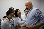 Vietnamese doctors from left, Yen Hoang Dinh, Ha Thanh Thi Nguyen, Dung Hong Doan, and Diem Hong Quang Vo react as Dr. Steve Charles shows off pictures of his grandchildren during a screening day to determine which patients will receive eye surgeries. Photo taken at the Ho Chi Minh City Eye Hospital on Monday, April 14, 2008...ORBIS Flying Eye Hospital brought doctors, nurses and specialists from all over the world to Ho Chi Minh City, Vietnam from April 7-18, 2008.  The ORBIS program contributed to the efforts of Ho Chi Minh City Eye Hospital in fighting avoidable blindness by educating local ophthalmologists to diagnose and manage pediatric blindness, retinal disease, oculoplastics, and blindness due to glaucoma.