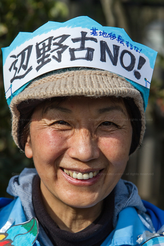 "A protestor wears a hat with ""Henoko -No!"" written on it at a rally to protest the construction of a new US military base at Henoko in Okinawa outside the Japanese National Diet building, Nagatacho, Tokyo, Japan Sunday January 25th 2015. Organisers say 7,000 people joined the protest forming a human chain around the Assembly Building."