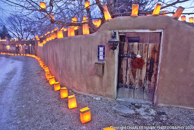 The arrival of dusk on Christmas eve finds walls and gates of Canyon Road in Santa Fe festooned with faralitos, each a paper bag containing a candle, which light up the night for visitors and locals celebrating the holiday.