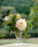 A glass is filled with a dahlia, basil and wild flowers