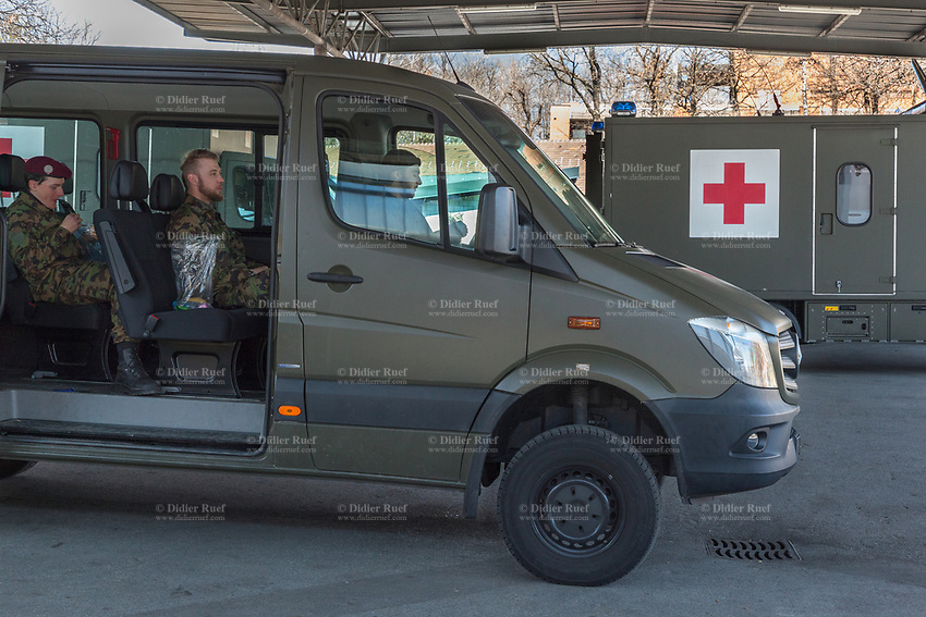 """Switzerland. Canton Ticino. Rivera. Monte Ceneri military base. Green military ambulances . Due to the spread of the coronavirus (also called Covid-19), the Federal Council has categorised the situation in the country as """"extraordinary"""". The army was called upon to provide logistical support and to offer its skills in terms of medical assistance (ambulances, field hospital, tents, nurses,..).The militia soldiers from medical troops were called by the Swiss army for the first time since World War II. Under the country's militia system, professional soldiers constitute a small part of the military and the rest are conscripts or volunteers aged 19 to 34 (in some cases up to 50). The soldiers seat in a van and eat their lunch. They are distant in order to avoid close contact and potential contamination by coronavirus. Safety healthy distance. Monte Ceneri is a mountain pass in the canton of Ticino. It connects the Magadino plain and the Vedeggio valley across the Prealps. 2.04.2020 © 2020 Didier Ruef"""