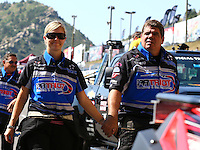 Jul. 20, 2014; Morrison, CO, USA; NHRA top fuel driver Jenna Haddock (left) walks with husband funny car driver Terry Haddock during the Mile High Nationals at Bandimere Speedway. Mandatory Credit: Mark J. Rebilas-