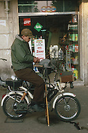 "April 27, 1990, Rome, Italy. Photographing for the book ""One day in the life of Italy"", this is an exploration of Rome. In Piazza Zama, a knife-sharpening vendor uses his bike to sharpen a tool."