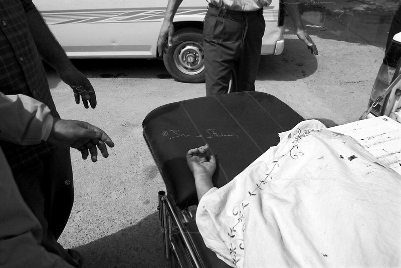 Baghdad, Iraq, April 5, 2003.Outside Al Kindi hospital emergency ward, aides cover up the body from an unidentified young boy killed at Ubeidi by a US bomb. More than 70 US bombardment victims were admitted in less than 2 hours after a B52 carpet bombing on the Northern outskirts, about a fifth of these were military personel.