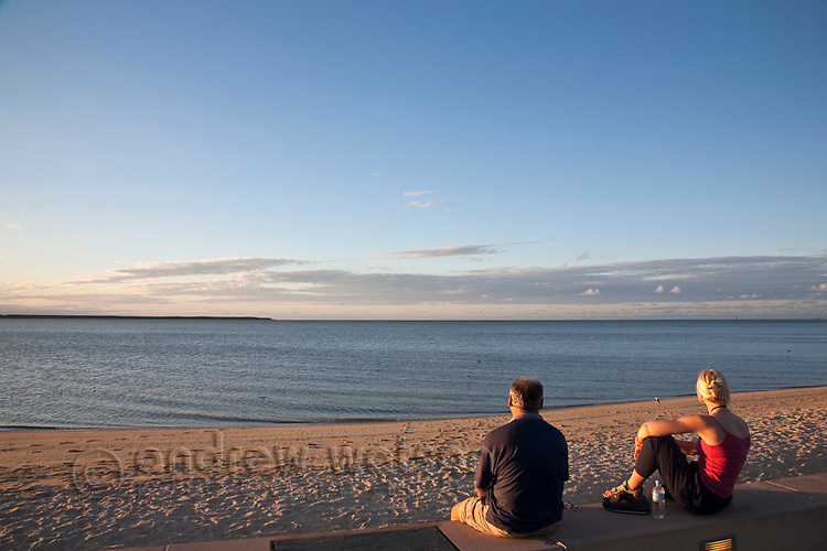 Couple looking out from Esplanade at sunset.  Cairns, Queensland, Australia
