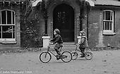 Little kids cycling passed the main building, Summerhill school, Leiston, Suffolk, UK. 1968.