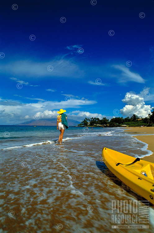 A woman walks along Wailea Beach with a yellow kayak in the foreground.