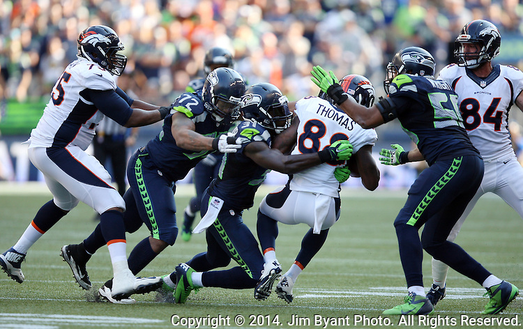 Seattle Seahawks   defensive end Michael Bennett (72) free safety Kam Chancellor (31) and linebacker K.J. wright team up to bring down  Denver Broncos wide receiver Demaryius Thomas (88) in the fourth quarter at CenturyLink Field in Seattle, Washington on September 21, 2014. The Seahawks won 26-20 in overtime.    ©2014. Jim Bryant Photo. All rights Reserved.