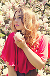 Thoughtful young woman holding a magnolia in her hand and wearing a long red summer dress