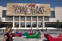 "Albania. Tirana. The National Museum of History on Skanderbeg Square. The National Museum of History is the national historical museum of Albania and the country's largest museum located in Albania. It was opened on 28 October 1981 and is 27,000 square metres in size, while 18,000 square metres are available for expositions. Above the entrance of the museum is a large mural mosaic titled The Albanians that depicts purported ancient to modern figures from Albania's history. The flag of Albania is a red flag with a silhouetted black double-headed eagle in the center. The red stands for bravery, strength and valor, while the double-headed eagle represents the sovereign state of Albania. The Skanderbeg Square is the main plaza in the centre of Tirana. The square is named after the Albanian national hero Gjergj Kastrioti Skënderbeu and the total area is about 40.000 square metres. The Skanderbeg Square is a pedestrian zone. Free Wifi offered by ALBtelecom SH. a. (a shortening of Albanian Telecom - ""Telekomi Shqiptar"") which was established as Albania's state company that provided telecommunications services through a fixed and mobile network. Colorful giant plastic forms (red, blue, green) for people to sit and relax while surfing the web. Tirana is the capital and most populous city of the Republic of Albania. The city is also the capital of the surrounding county of Tirana, one of 12 constituent counties of the country. 27.5.2018 © 2018 Didier Ruef"