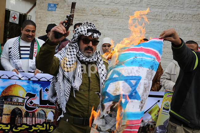 Palestinians burn an Israeli flag and a U.S. flag during a protest against Trump's decision to recognize Jerusalem as the capital of Israel, in Gaza City December 11, 2017. Photo by Ashraf Amra