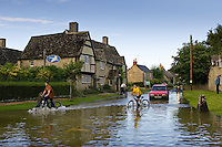 Children ride their bikes through  flood water in Minster Lovell, The Cotswolds, Oxfordshire, England, United Kingdom
