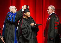 NWA Democrat-Gazette/BEN GOFF @NWABENGOFF<br /> Dr. Joe Steinmetz (left), chancellor of the University of Arkansas, and Mark Waldrip (right), vice chairman of the university board of trustees, present an honorary degree to architect Chris Hinton-Lee Saturday, May 11, 2019, during the University of Arkansas all university commencement ceremony in Bud Walton Arena in Fayetteville. Hinton-Lee also delivered the commencement address.