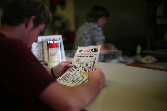 A customer reads the menu at The White Flash in downtown Jackson, Ky., on Thursday, Oct. 13, 2011. The diner prides itself on low prices and high customer interaction. Photo by Tessa Lighty