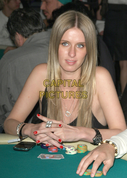NICKY HILTON .7th Annual World Poker Tour Invitational held at Commerce Casino, Los Angeles, California , USA, 28 February 2009..half length playing game sitting at table  black vest tattoos chips gambling ring necklace watch hair down blackberry red painted finger nails nail varnish .CAP/ADM/KB.©Kevan Brooks/Admedia/Capital PIctures