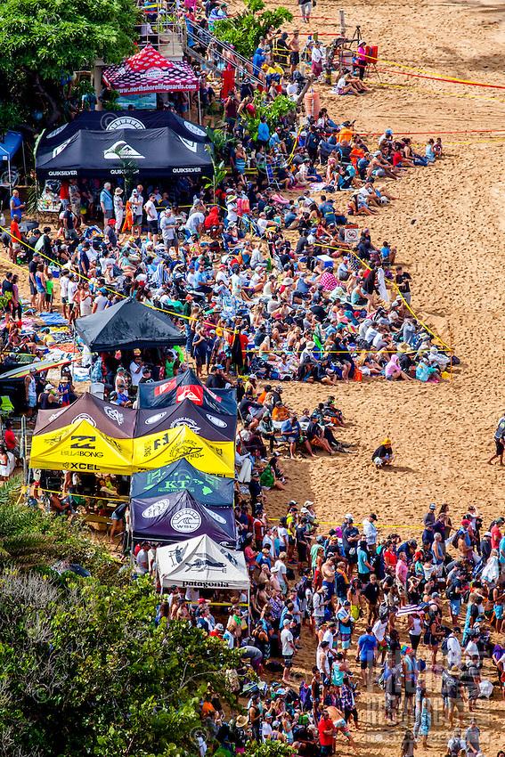A huge crowd of spectators on the beach watch the 2016 Big Wave Eddie Aikau Contest, Waimea Bay, North Shore, O'ahu.