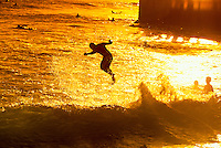 Man in silhouette, bodyboarding aerial acrobatics in waves at sunset; Waikiki Beach, Oahu