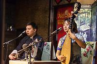 """Suzhou, Jiangsu, China.  Young Woman Playing a Pipa, Young Man Playing a """"Three Strings."""""""