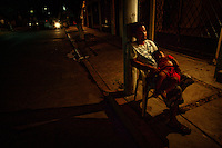 Acapulco, Mexico, February 17, 2012 – A father and son sleep in a chair waiting for the child's mother to finish work at her enchilada stand in the community on the Bahia De Puerto Marquez.