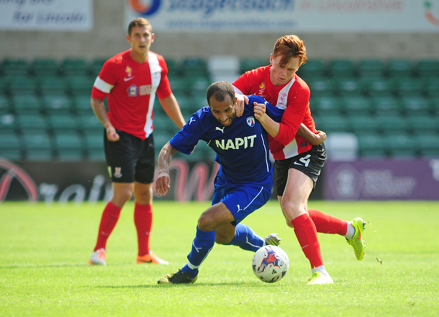 Chesterfield's Romy Boco is fouled by Lincoln City's Jon Nolan<br /> <br /> Photographer Chris Vaughan/CameraSport<br /> <br /> Football - Friendly - Lincoln City v Chesterfield - Saturday 19th July 2014 - Sincil Bank Stadium - Lincoln<br /> <br /> &copy; CameraSport - 43 Linden Ave. Countesthorpe. Leicester. England. LE8 5PG - Tel: +44 (0) 116 277 4147 - admin@camerasport.com - www.camerasport.com